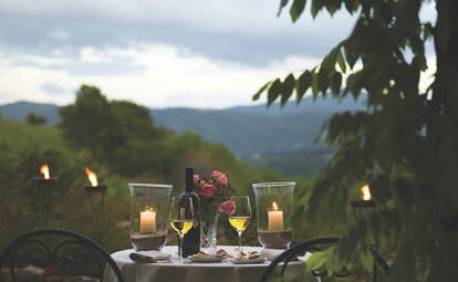Dining experience at the Hotel Villa di monte solare with a candle lit dinner set up outside overlooking the mountains