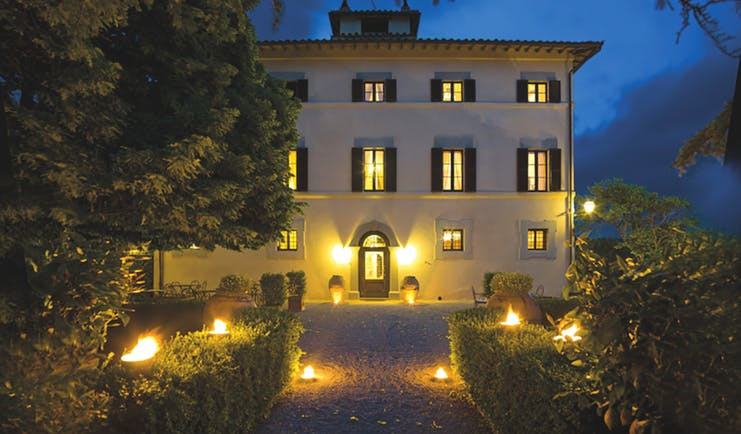 Hotel Villa di Monte Solare exterior at night, large white building with yellow rectangular windows with black shutters