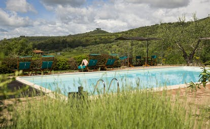 View of the rectangular pool at the hotel villa di monte solare in umbria with green mountains in the background