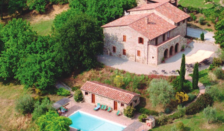 View of the hotel villa di monte solare from above, showcasing the swimming pool and multiple buildings amongst the green countryside