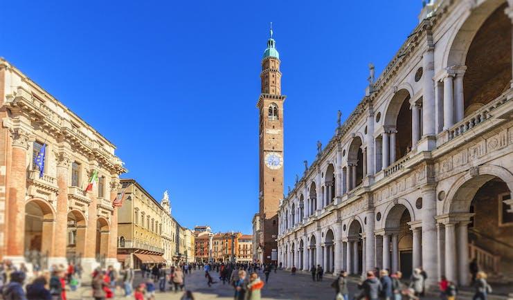 Tall campanile between arcaded buildings of Palladio in the Piazza dei Signori in Vicenza