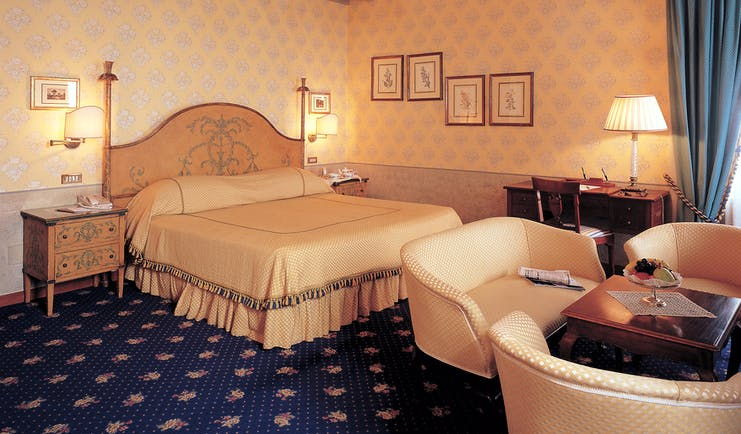 Bedroom with large double bed, chandelier, table and chairs