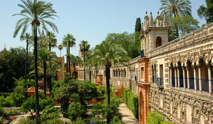 Palm trees and beds of flowers outside wall of the Alcazar in Seville