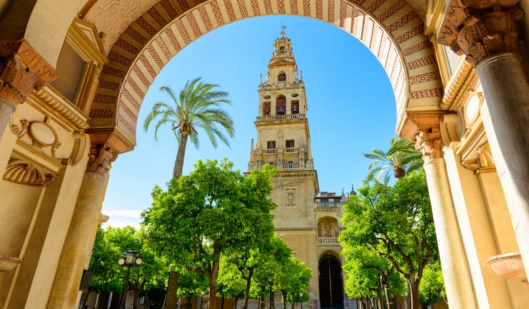 The spire of the Mezquita cathedral in Cordoba seen through an ornate Moorish stone arch