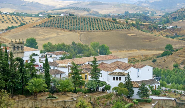 White washed village houses in landscape of yellow sunburnt fields at Ronda in Andalusia