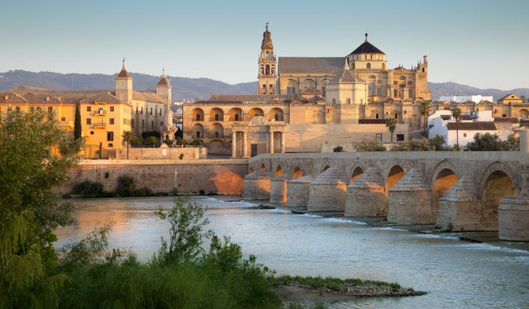 Pink tinged sunlight on the Mezquita cathedral by the river in Cordoba