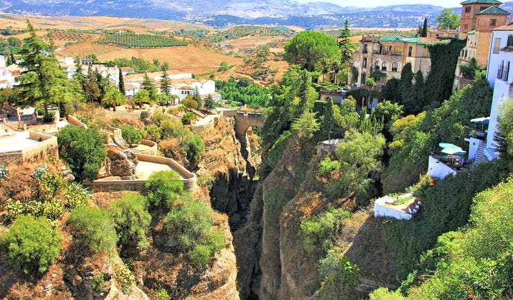 Deep stone gorge with houses on either side and greenery of trees dotted about at Ronda in Andalusia