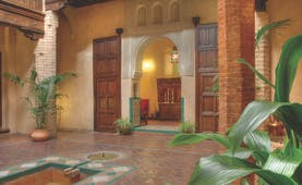 Casa Morisca patio with brick pillars, an archway and wooden doors