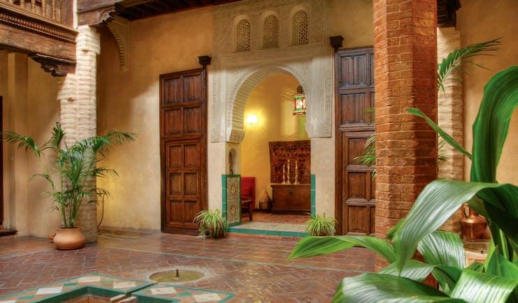 Casa Morisca patio with brick pillars, an archway and wooden doors