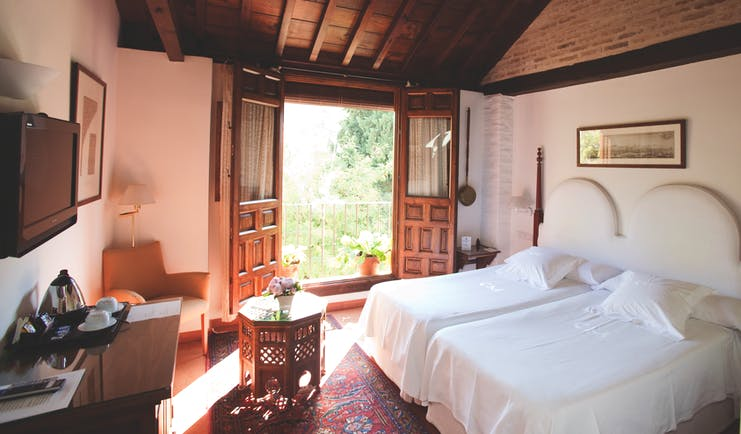 Standard room at the Casa Morisca with a double bed, television and double wooden doors leading onto a balcony