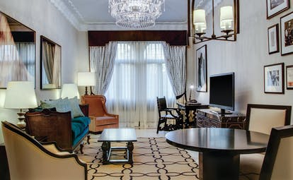 Executive suite living room with large crystal chandelier, television, draping curtains and velvet armchairs
