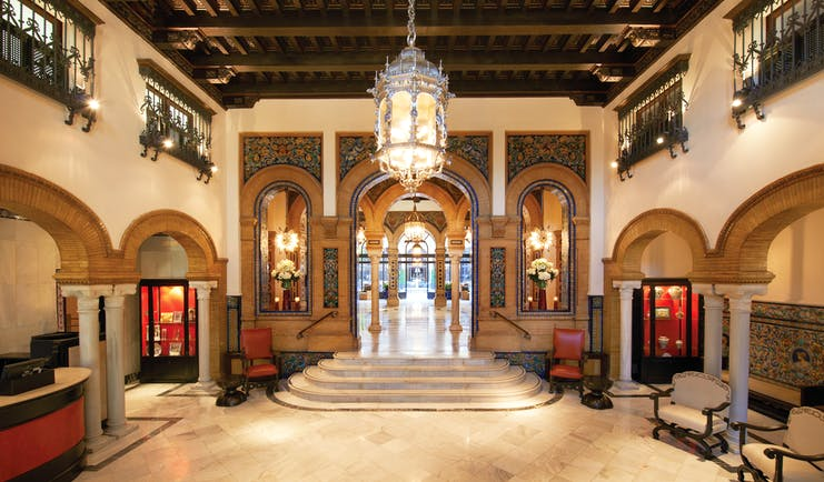 Hotel lobby with pillars, staircases and large chandelier