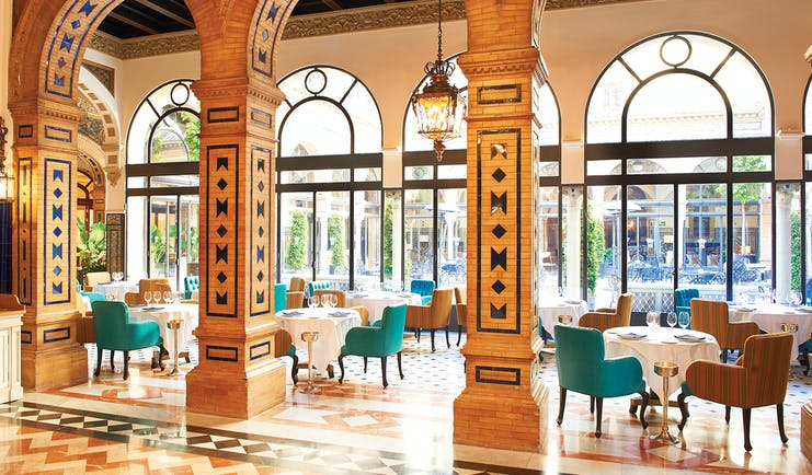 Restaurant with large arching pillars and dining table seating area