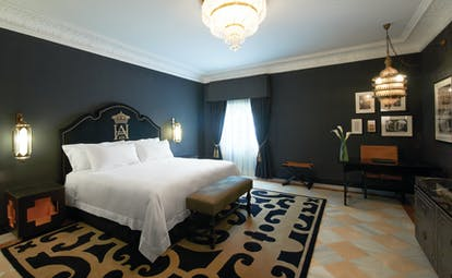 Suite with large double bed, chandelier, television and chairs