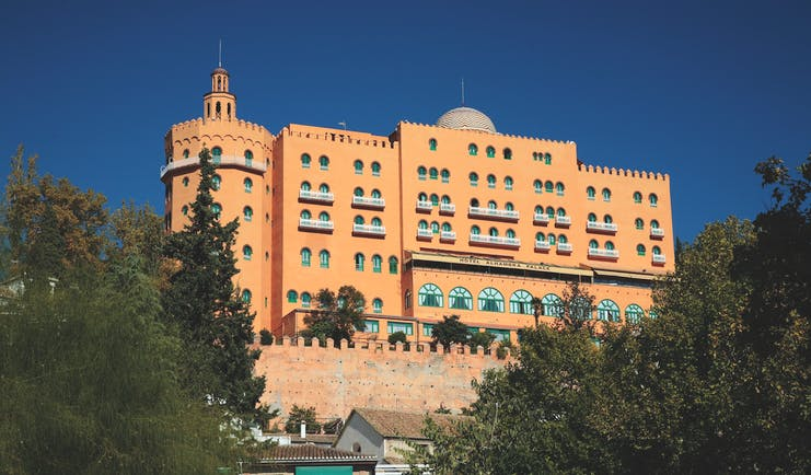 Exterior of the Hotel Alhambra Palace, a large orange building with small green windows