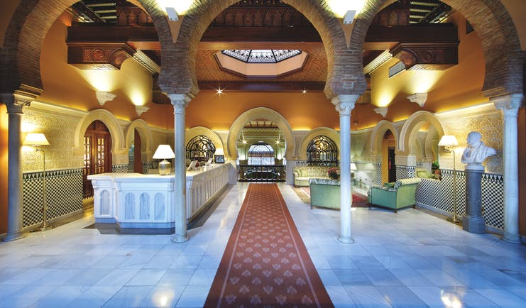 Reception at the Hotel Alhambra Palace with large archways with pillars and green seating areas