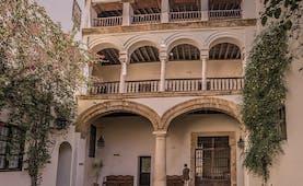 Las Casas de la Juderia Andalucia exterior stone walls columns grass trees