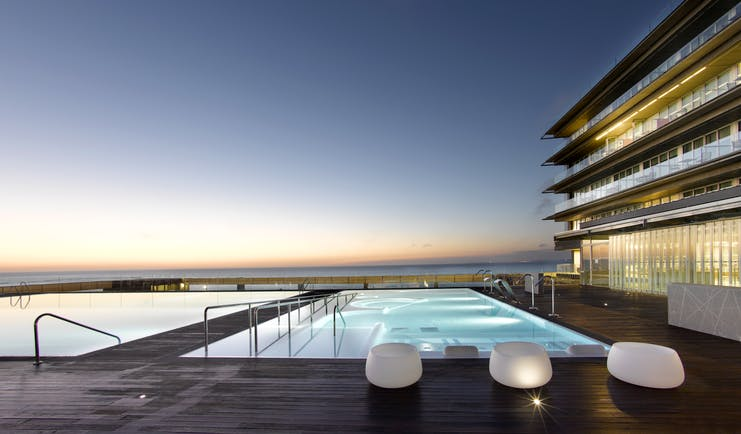Parador de Cadiz Hotel Atlantico poolside, decking, pool lit up at night, terrace overlooking sea