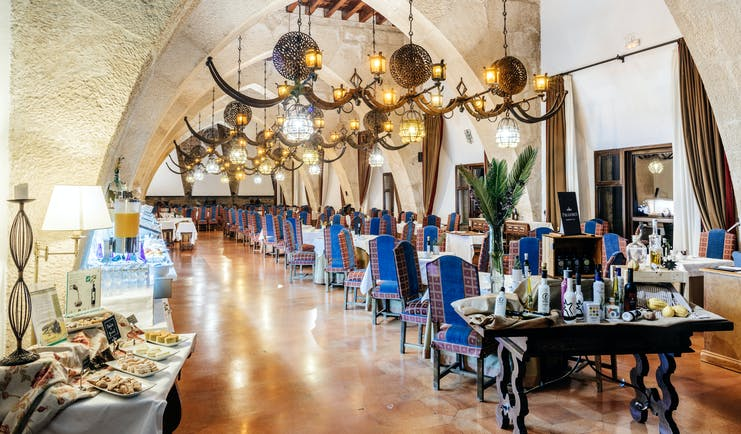 Parador de Jaen arcaded dining room with chandeliers and blue backed chairs