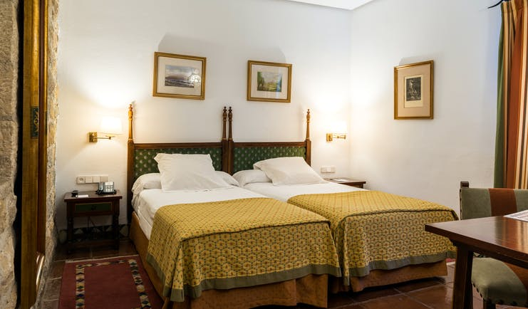Twin bedded room with white alls and yellow bedspreads at the Parador de Jaen