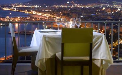 Parador de Malaga Gibralfaro dining terrace, table set for two, balcony overlooking the coast, town and mountain at night