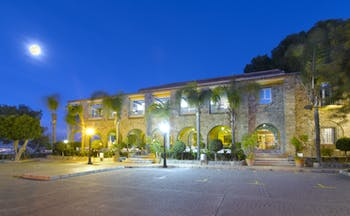 Parador de Malaga Gibralfaro exterior at night, traditional architecture, moon in night sky, pine trees