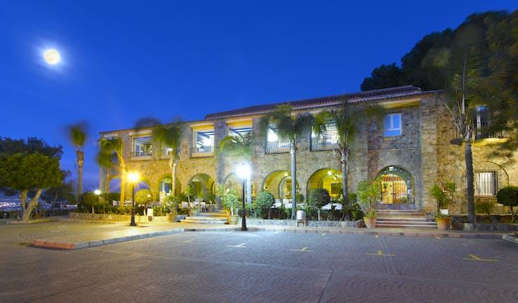 Parador de Malaga Gibralfaro exterior at night, traditional architecture, moon in night sky, pine trees