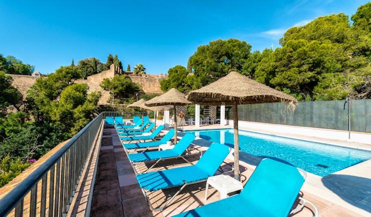 Parador de Malaga Gibralfaro pool, sun loungers, pine trees in background