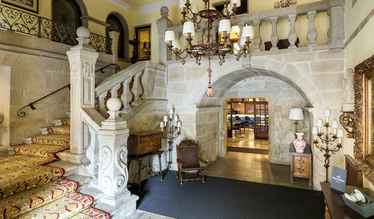 Parador de Pontevedra lobby, ornate stone staircase, carvings, carpet, chandelier, traditional decor