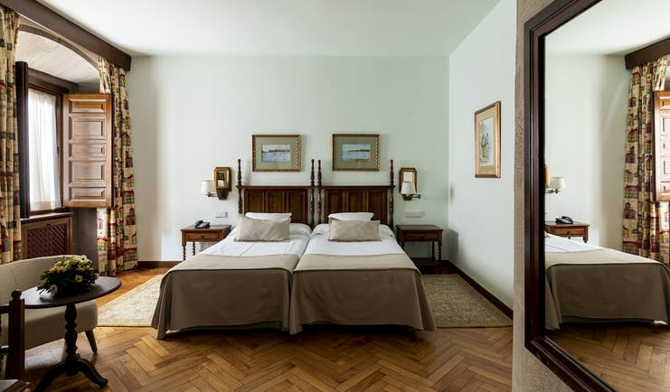 Parador de Pontevedra standard room, twin beds, wooden floors, shuttered windows, traditional decor