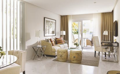 Puente Romano Marbella deluxe two bedroom suite living area sofa chairs balcony
