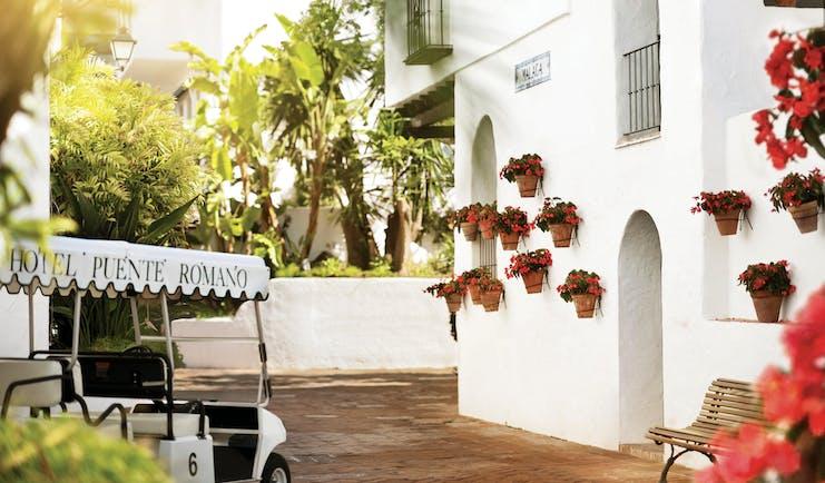 Puente Romano Marbella exterior white building plant pots red flowers