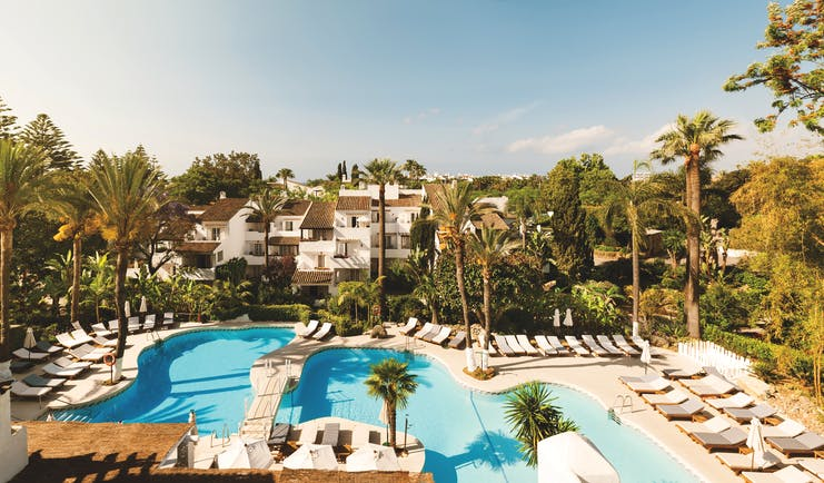 Puente Romano Marbella pool sun loungers palm trees