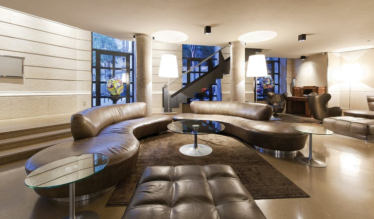 Hotel Claris Barcelona lobby leather sofas glass table stylish décor