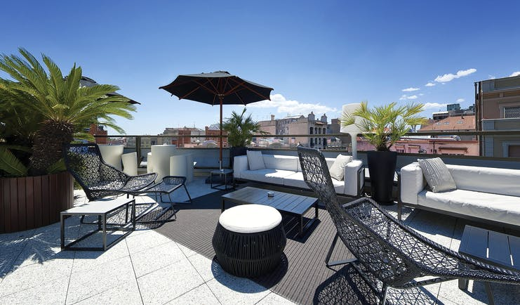 Hotel Claris Barcelona terrace rooftop seating area loungers umbrella city views