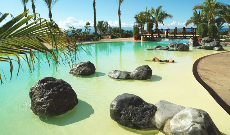 Abama Tenerife pool terrace palm trees rocks in water
