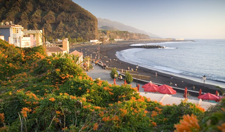 Black sand beach with white houses on land near Los Llanos de Aridane on La Palma in the Canaries