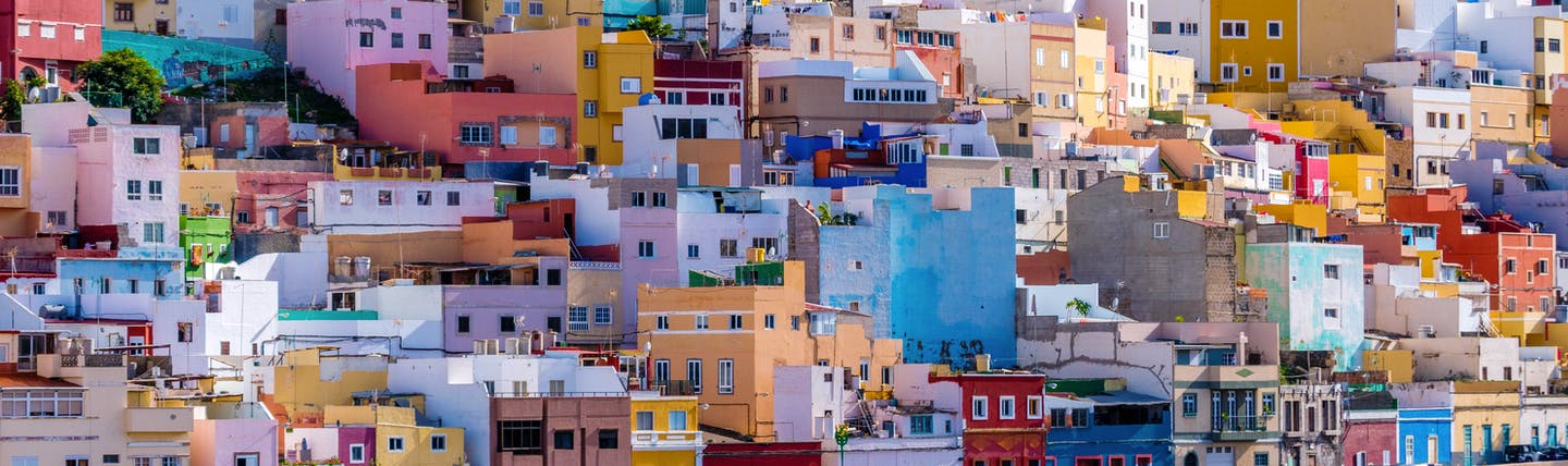 Brightly coloured houses of reds, pinks, blues and yellow on hillside with cross in sky in San Juan Las Palmas on Gran Canaria