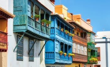 Galleried houses with balconies of pot plants all painted different colours in Santa Cruz de la Palma