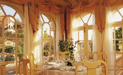 Indoor restaurant with gold colour scheme and draping curtains