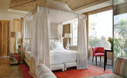 Villa bedroom with large white four poster bed  and sofa