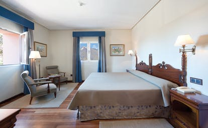Bedroom with large double bed, arm chair and windows
