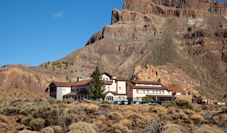 Exterior of hotel shown in front of huge mountain