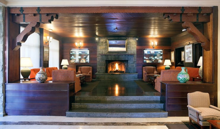 Lobby area with fire place, sofas and arm chairs and wood pannelled ceilings