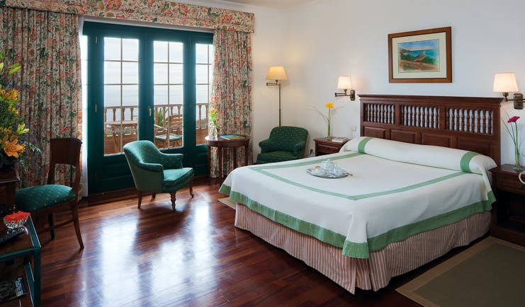 Bedroom with doors opening onto a terrace balcony and with a double bed