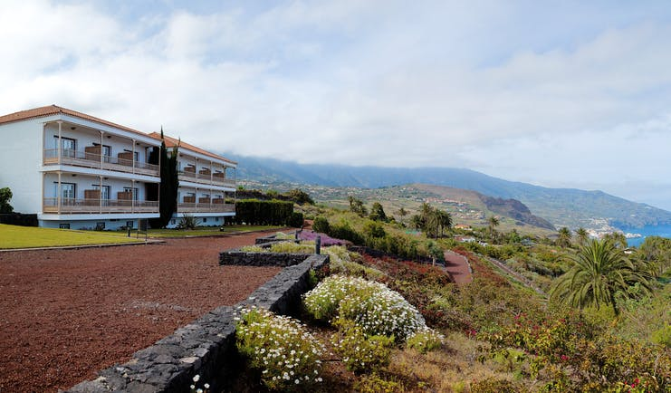 Exterior of hotel with white building and looking out over the gardens and sea