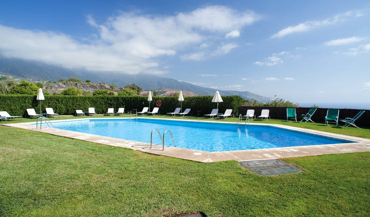 Outdoor swiming pool with grass surface nearby and white sunloungers and umbrellas set up around the edge of the pool