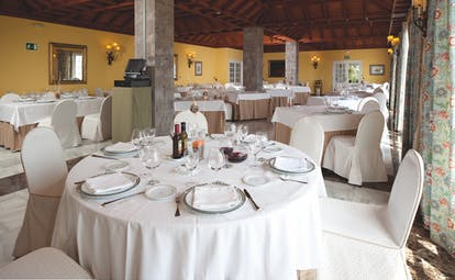 Restaurant with dining tables set out with wood pannelled ceilings and stone pillars