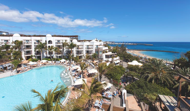 Princesa Yaiza pool aerial shot, beach and sea in background, hotel buildings, pool deck, sun loungers, palm trees