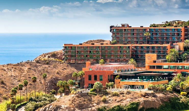 Exterior of hotel buildings amongst hills looking out over the sea